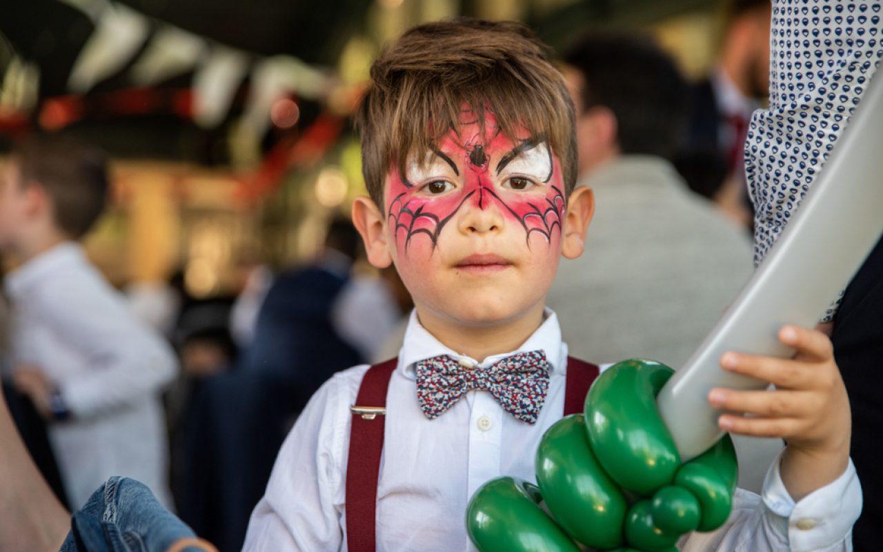 Enfant avec un nœud papillon maquillage Spiderman qui tient un ballon
